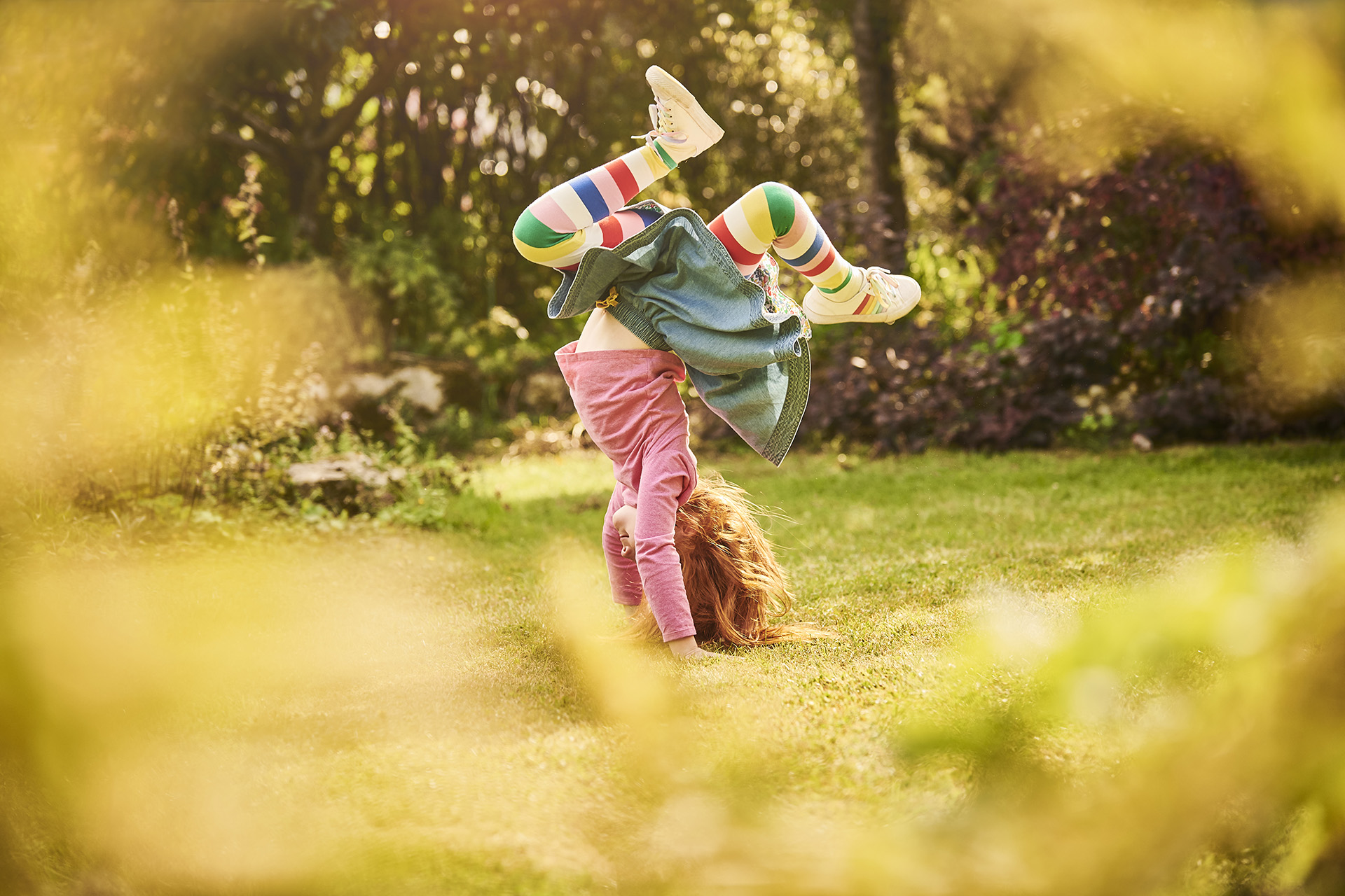 A young girl with stripy tights doing a handstand in her garden
