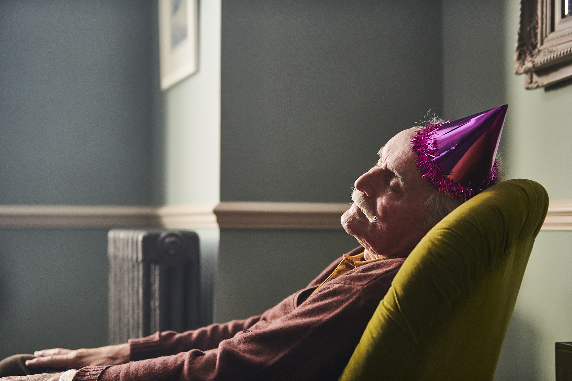 An elderly man having a nap on an armchair