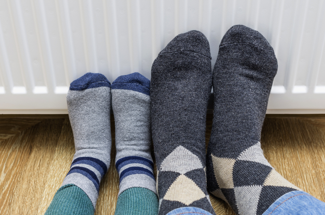 Two people's feet in socks warming them against a radiator