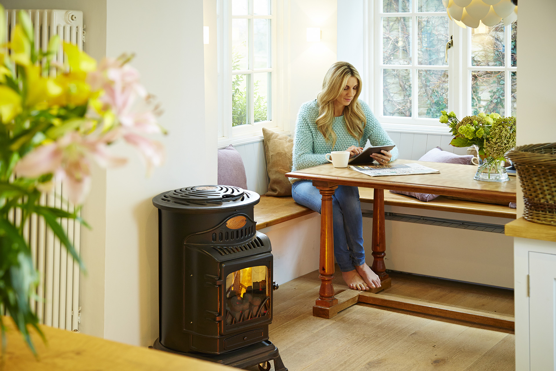 A lady in her kitchen with a Calor portable gas heater