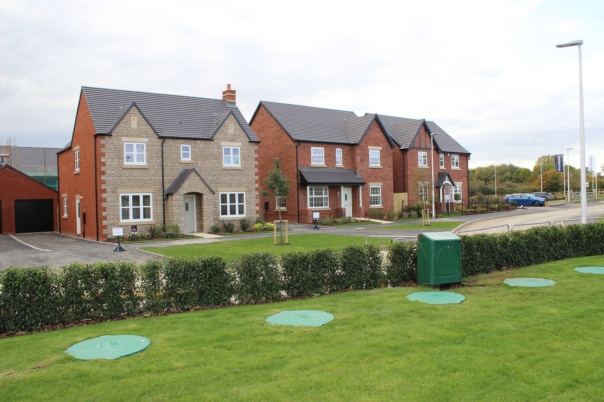 Five LPG underground tank covers in front of three large detached houses