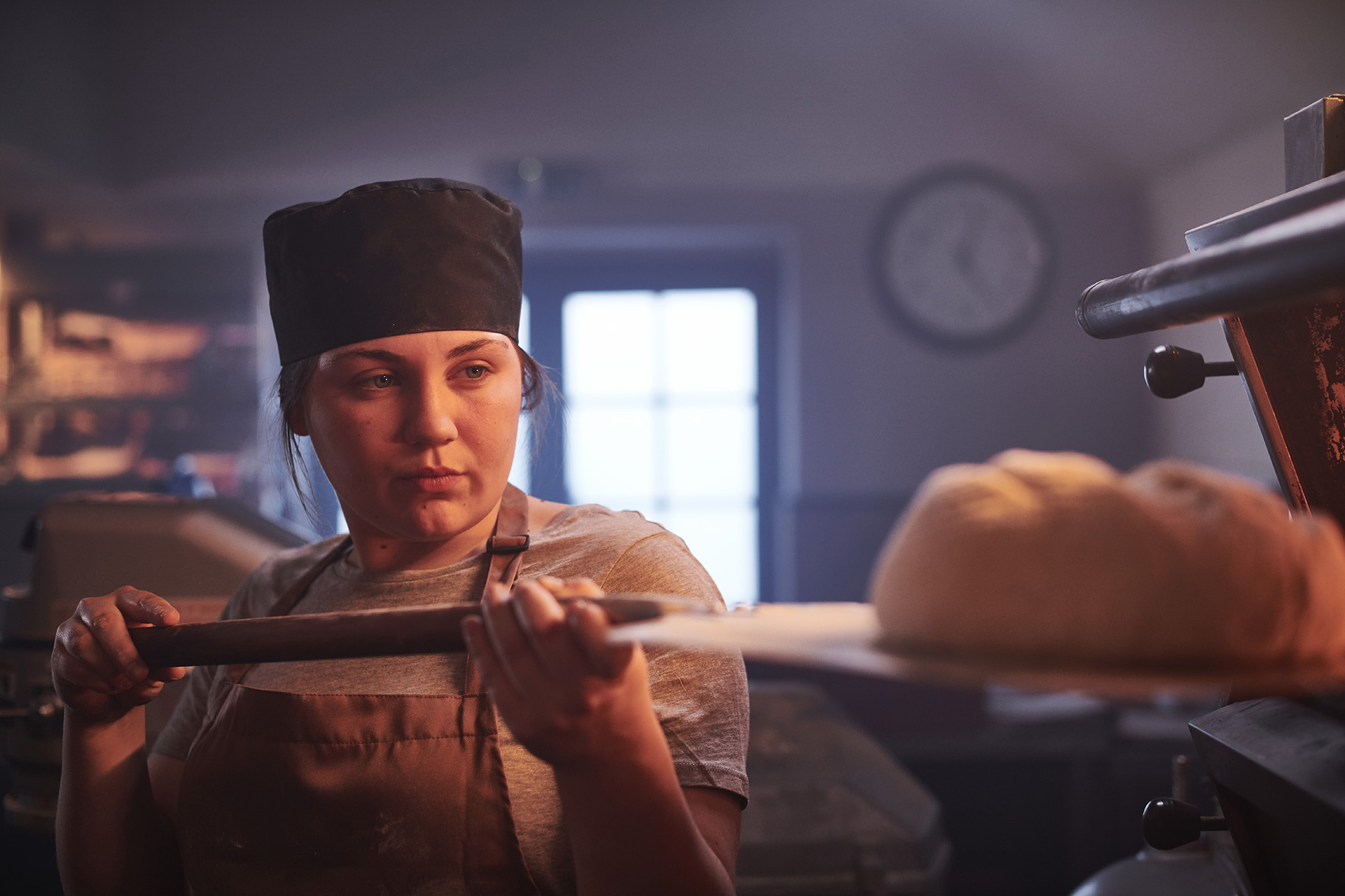 A baker removing bread from an oven