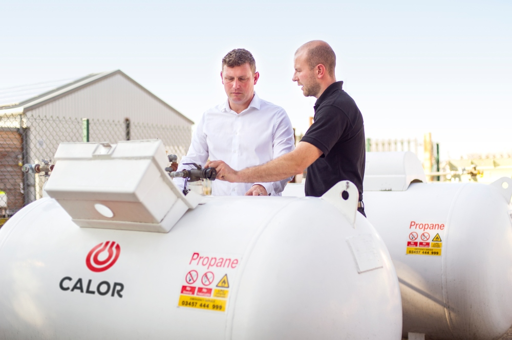 Two Calor employees inspecting an above ground LPG tank