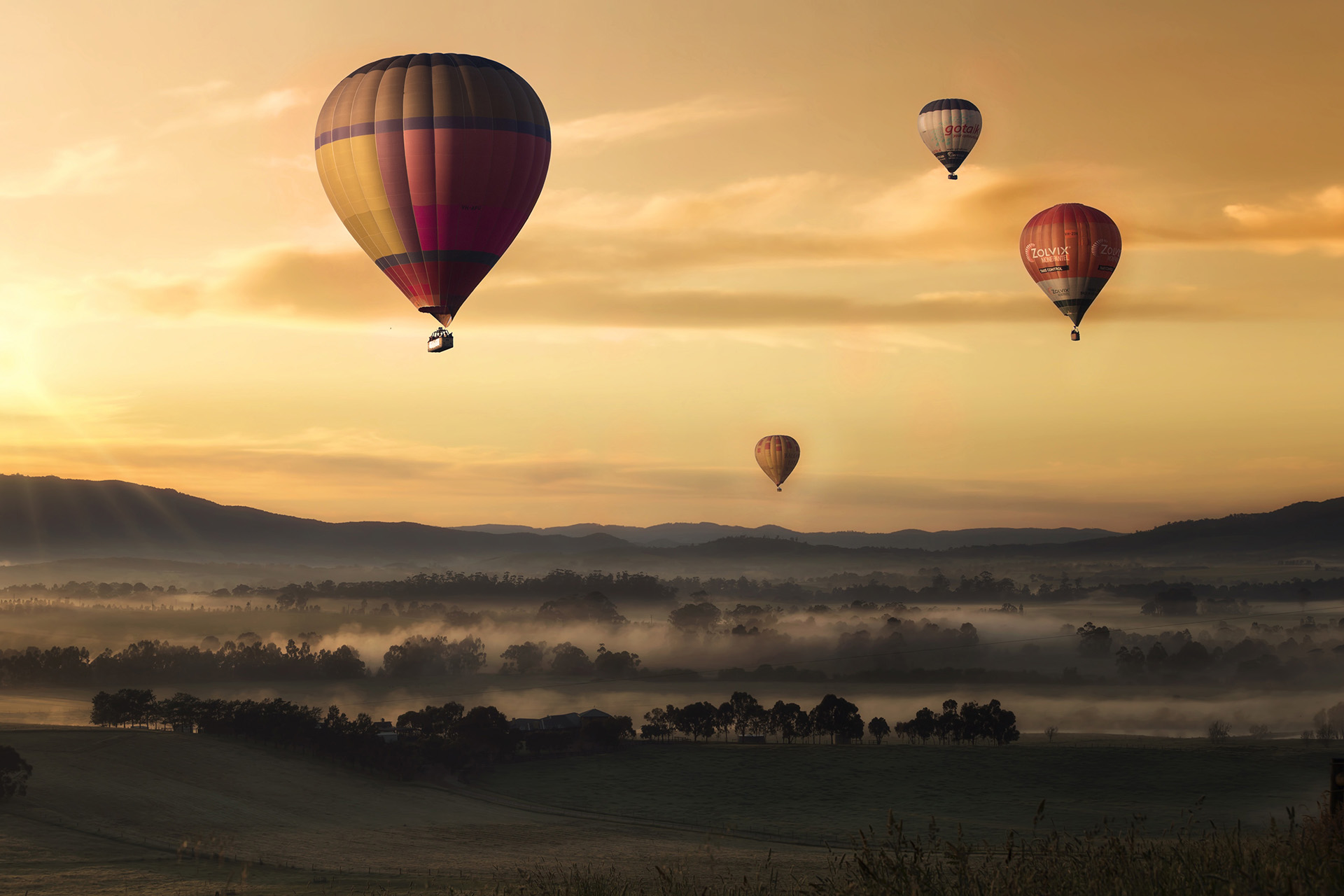 Four hot air balloons flying at dusk