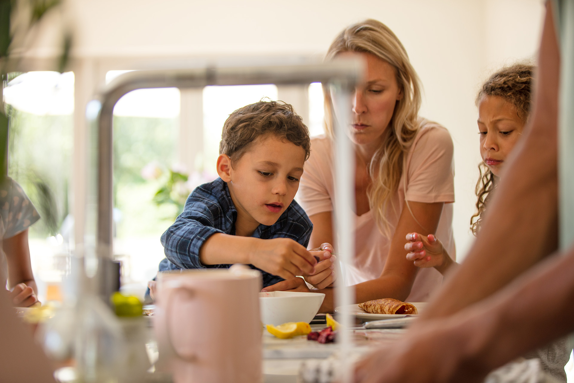 A father is washing his hands in the foreground, whilst the rest of the family eat their breakfast in the background