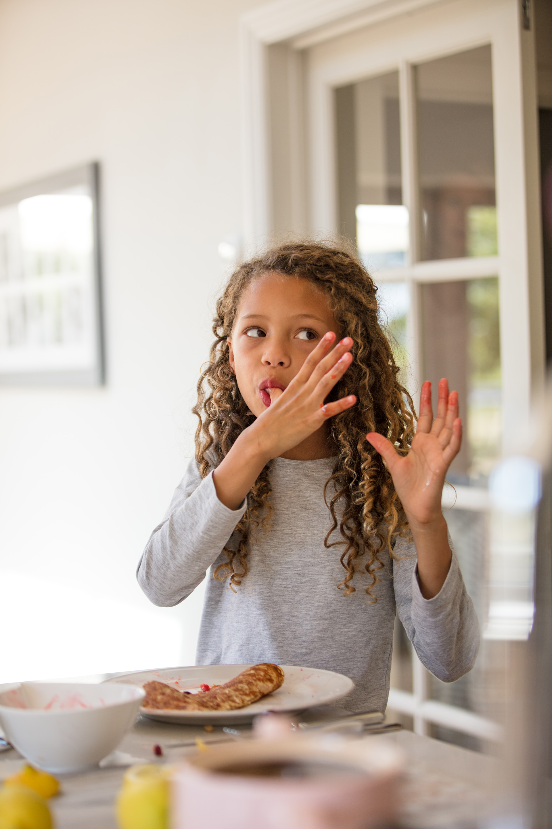 A child licking her thumb as she stands to eat her pancakes