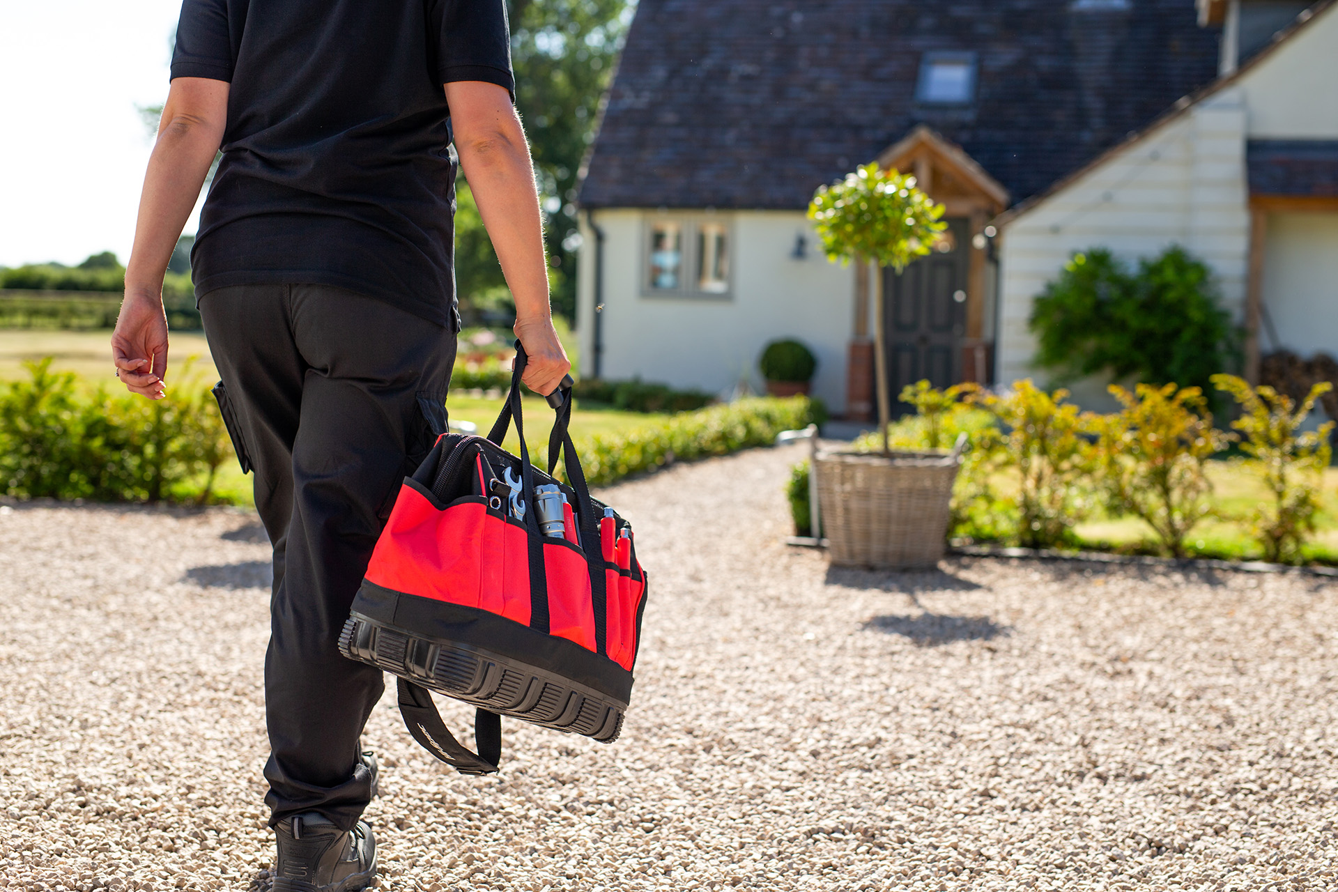 A Calor employee holding a tool bag and walking towards a Calor customer's house