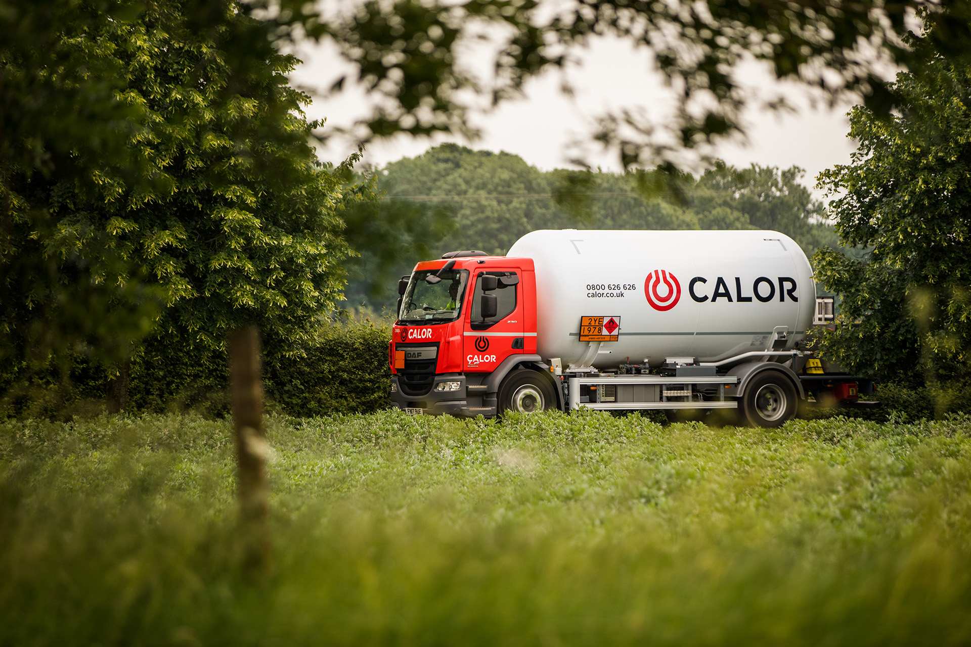 A side view of a Calor lorry driving through the countryside