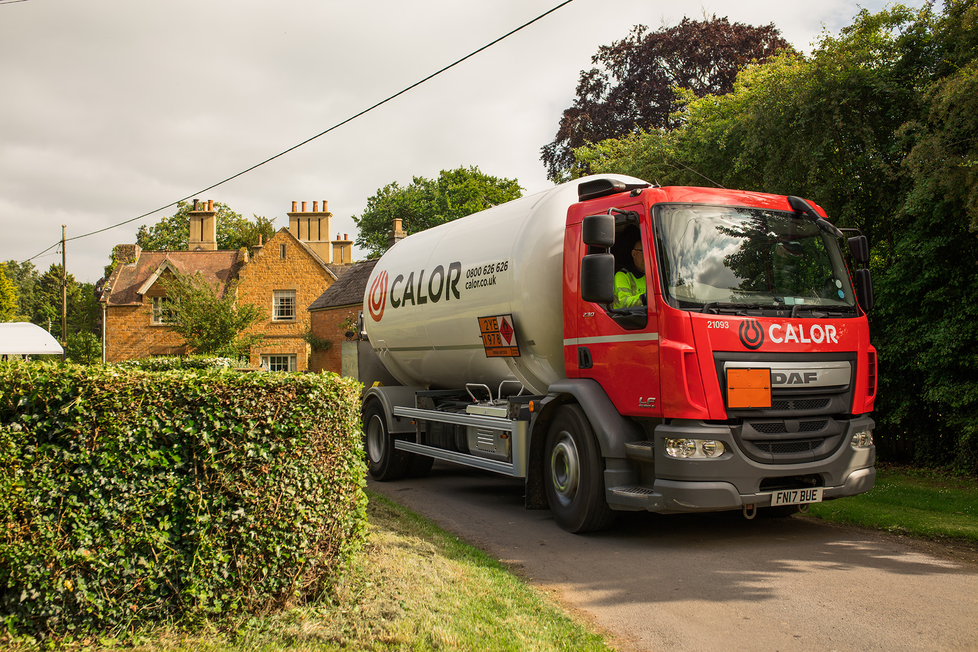 A Calor lorry driving on a narrow road in a rural village