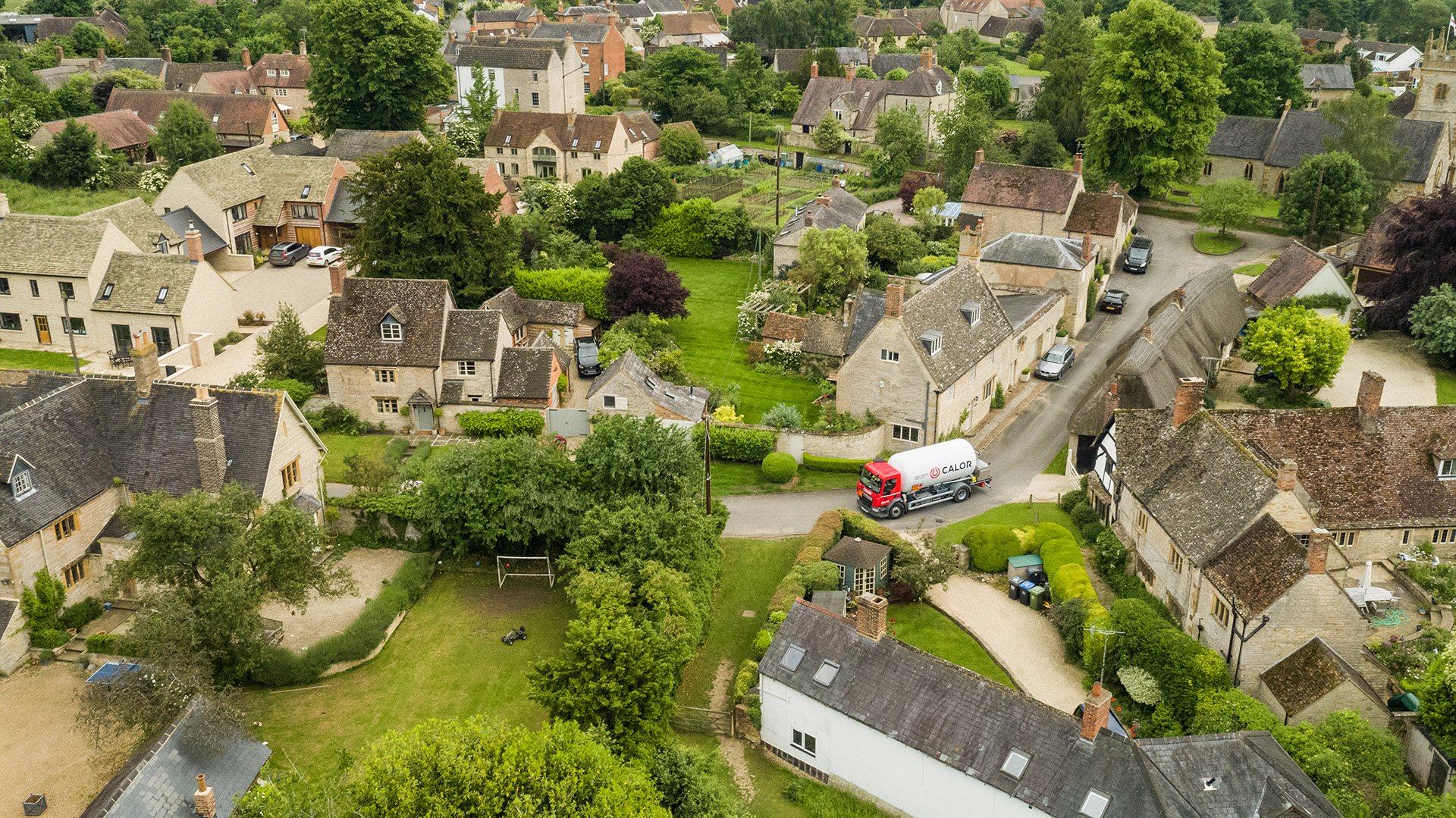 An aerial view of a Calor lorry driving through a rural village