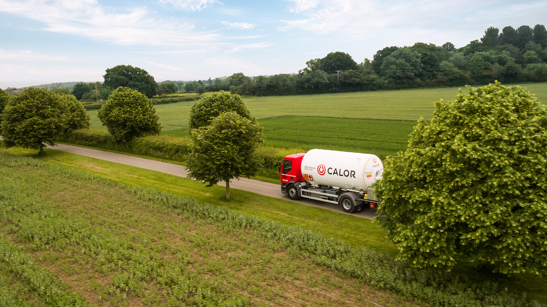 A Calor lorry driving in between green meadows in the countryside